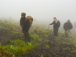 Approaching the Nyiragongo volcano summit through clouds with two armed rangers