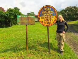 Posing at Kibati ranger station with the bullet-ridden signpost of Virunga National Park