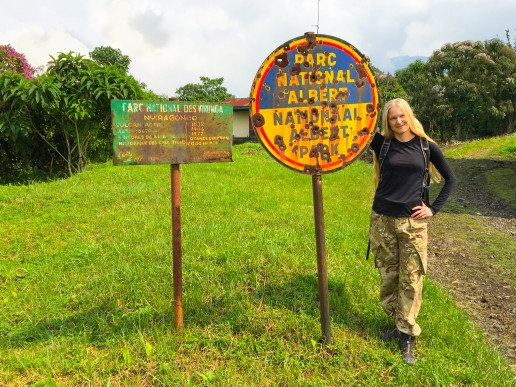 Posing at Kibati ranger station with the bullet-ridden signpost of Virunga National Park