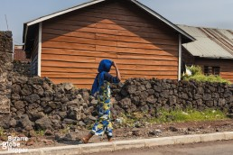 Awoman walking in the street in Goma, DRC, in front of a wall made out of the volcanic rock, left from the last eruption of Nyiragongo.